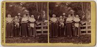 Four Shaker women and three Shaker men posed by fence