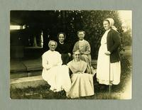 Group of five women outside near building [front]