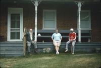 Woman and two men sitting on porch of Sisters' section of nunnery house at Snow Hill Cloister