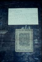 Eight dollar bill in Continental currency with note at Snow Hill Cloister