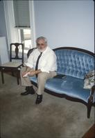 Man sitting on loveseat in room at Snow Hill Cloister