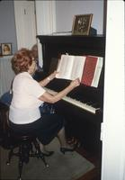 Woman playing piano in room at Snow Hill Cloister