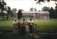 Men playing guitars in front of Sisters' house at Snow Hill Cloister