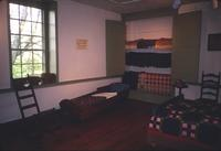 Coverlets in cupboard and adult cradle in room at Snow Hill Cloister
