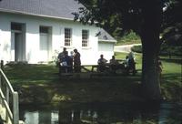 People on lawn in front of church at Snow Hill Cloister