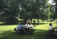 People sitting at picnic tables on lawn at Snow Hill Cloister