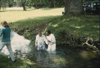 Men in creek during baptism service at Snow Hill Cloister