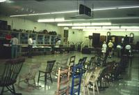 People perusing chairs and pottery in Horst Auction House at Ephrata, Pa.