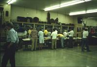 People perusing textiles and pottery in Horst Auction House at Ephrata, Pa.