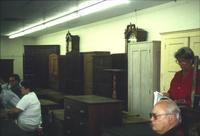 People, chests, cabinets, and grandfather clocks in Horst Auction House at Ephrata, Pa.
