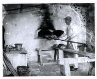 Baker unloading large loaves of bread from a bake oven