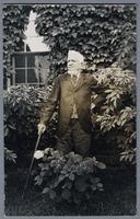 Conrad Baust - portrait of man in frock coat and cane standing in front of ivy covered building, taken August 1927 [front]