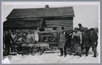 Amana farm workers with portable tractor powered saw [front]