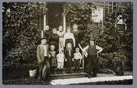 Group photograph on steps of a frame Amana dwelling [front]