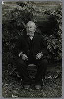 Caspar Grimm portrait on post card stock of a Main Amana resident seated on wooden chair with brick wall in background, ca. 1915
