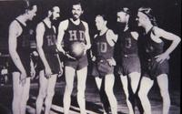 Members of the House of David basketball team posed in uniform around John Tucker holding a basketball [slide]