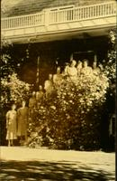 Women and men standing on exterior staircase that is covered in vines [slide]