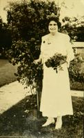 Mary Purnell dressed in white posed next to a bush while holding a bouquet of flowers [slide]