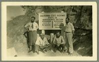 "Four men posing with ""California state highway"" sign"