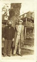 Frye and Tucker posing in front of a tree and a house