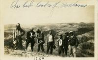Seven men posing while walking through the Bad Lands of Montana