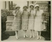Eunice Bauscke, Myrtle Faulk, Mabel Blackburn, and Bertha Bell dressed in identical white, ruffled dresses, pointing at the photographer
