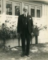 Photograph of Andrew Bell posing in front of the exterior of a house