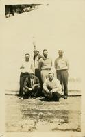 Six men posing in front of a large pile of snow