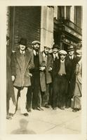 Eight men in coats and hats posing in front of a building
