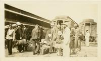 Group of men with luggage outside a train