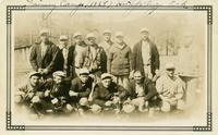 Fourteen members of the House of David baseball team posing on the baseball diamond