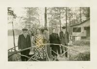 People posing on a bridge with a house and pond visible in the background