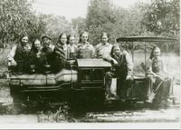 Nine young men posing with the miniature railroad