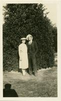 George Anderson and Exa Mae Nelson posing in front of a large holly tree