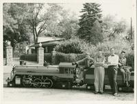Bobby Gahnsan, Walter Gahnsan, Burt Mitchell, Pete Scott posing with the miniature railroad