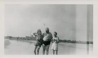 Two women and a man in dressed in bathing suits at the beach