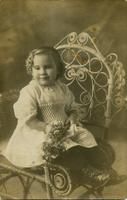 Young girl posed on a chair holding flowers