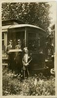 Three men posing with a railroad car