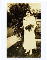 Woman dressed in white posed next to a bush while holding a bouquet of flowers
