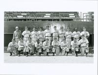 Auscos baseball team posed in uniform against dugout