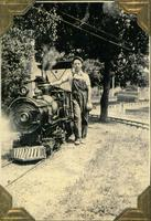 Boy standing next to miniature railroad