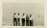 Five men in hats posing on the beach