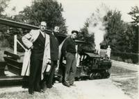 Three men posing in front of the miniature railroad