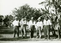 Five men posed on grass with trees