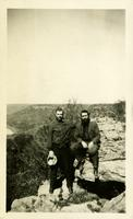 Two men posing on a rock formation with a valley in the distance