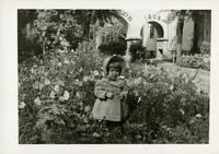 Young girl posed in flower bed with House of David arches partially visible behind her