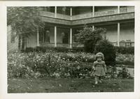 Young girl in front of a row of bushes and flowers with a building in the background