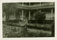 Young girl held by woman in front of a flower bed with a building in the background